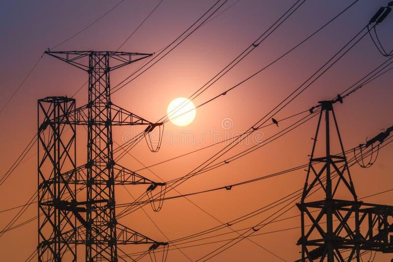 在日落期间的高压钢传输塔 免版税库存照片