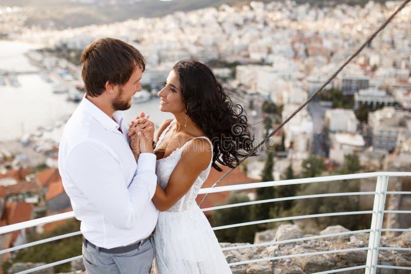 在日落期间,一对美好的浪漫微笑的夫妇的鸟瞰图,摆在拥抱在老城市和海港后, 库存图片