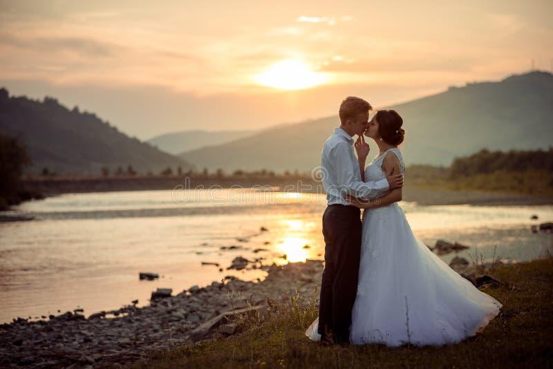在日落期间,可爱的新婚佳偶夫妇在河岸轻轻地亲吻 库存照片