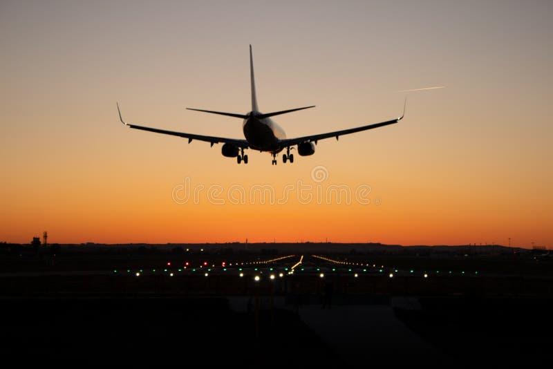 在日落期间,商业乘客飞机在机场跑道登陆 免版税库存照片