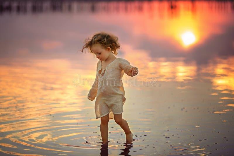 在日落期间,小女孩在海滩走 库存图片