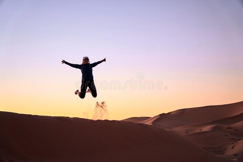 在日落期间,旅游女孩跳在沙漠沙丘 免版税库存照片