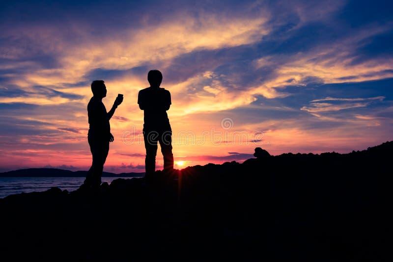 在日落期间,现出轮廓在clift的双人身分 免版税库存照片