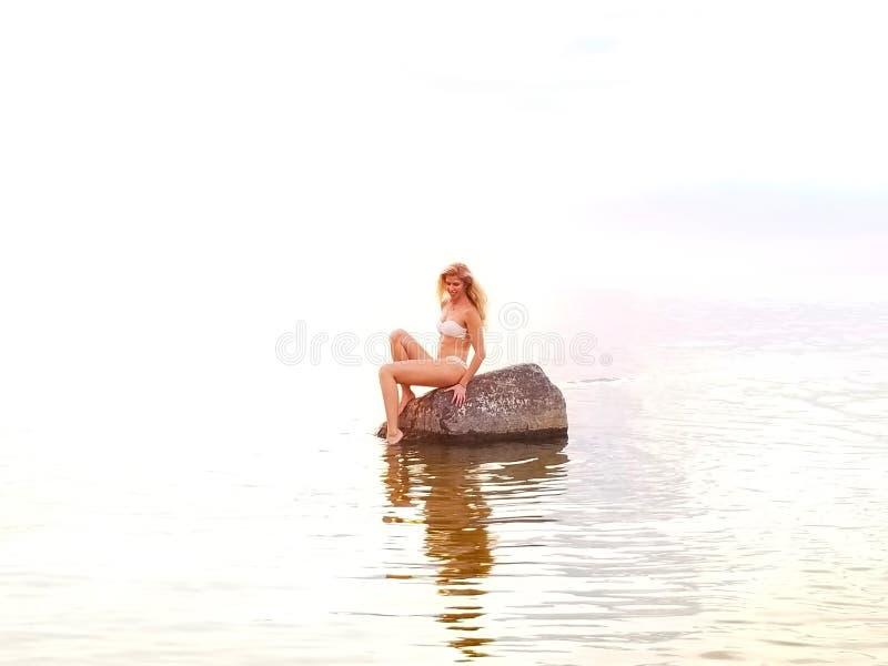 在日落期间,白色比基尼泳装的美丽的金发碧眼的女人在水中坐一个石身分 库存图片
