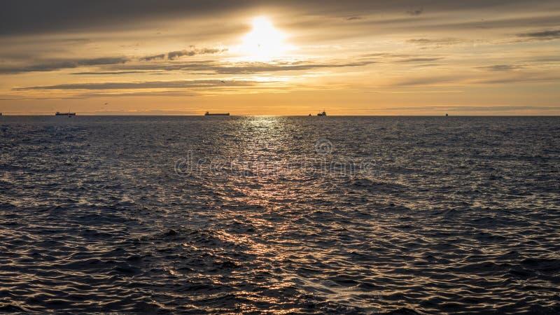 在日落期间,船剪影很远被看见 库存图片