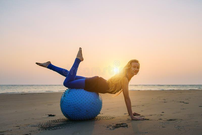 在日落期间,长发金发碧眼的女人参与一个训练球的皮拉提斯在海滩 舒展她的身体的适合妇女 免版税图库摄影