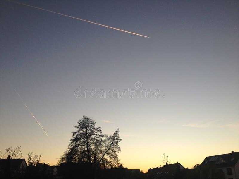 在日落期间的空中飞机 库存图片