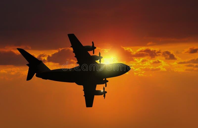 在日落期间的飞机飞行 免版税库存图片