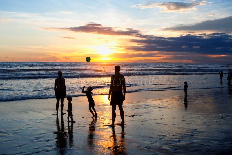 在日落期间,孩子和成人打在海滩的球 免版税库存照片