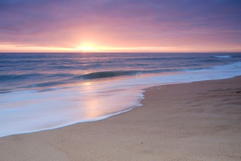 在日落期间,镇静海滩挥动 免版税库存图片