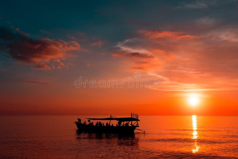 在日落海滩的美好的日落与船 图库摄影