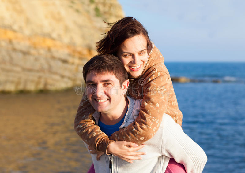 在日落海背景的愉快的年轻夫妇 库存图片