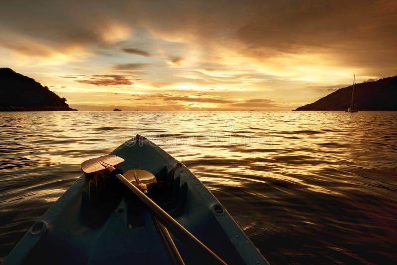 在日落海背景的皮船弓 免版税库存照片