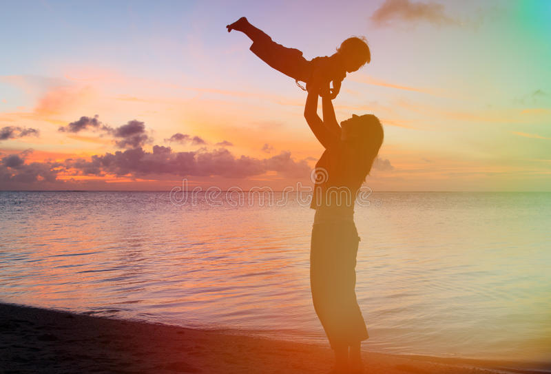 在日落海滩的母亲和婴孩乐趣 图库摄影