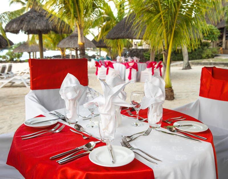 在日落海滩的浪漫晚餐 餐位餐具表 免版税图库摄影