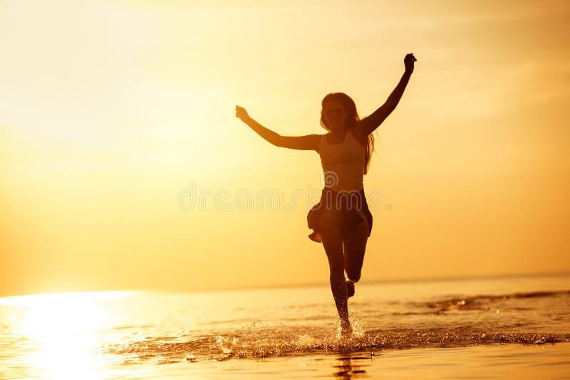 在日落湖跑的愉快的女孩 免版税库存照片