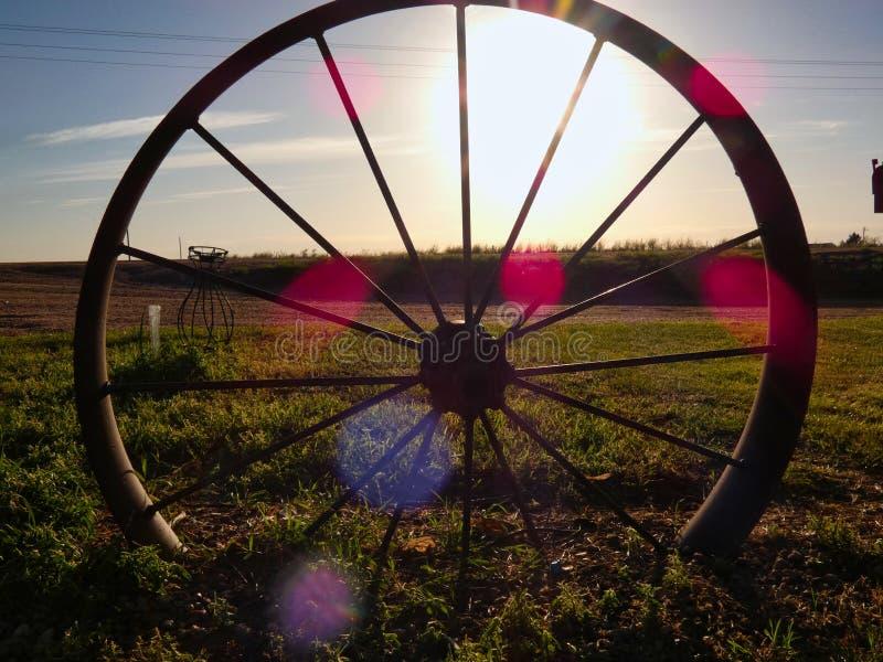 在日落现出轮廓的古色古香的马车车轮 免版税库存照片