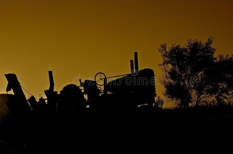 在日落现出轮廓的拖拉机 库存照片