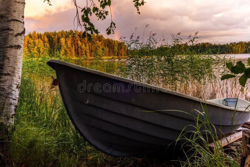 在日落的一艘木划艇在镇静Saimaa湖的岸在芬兰在与彩虹- 1的北欧天空下 免版税库存图片
