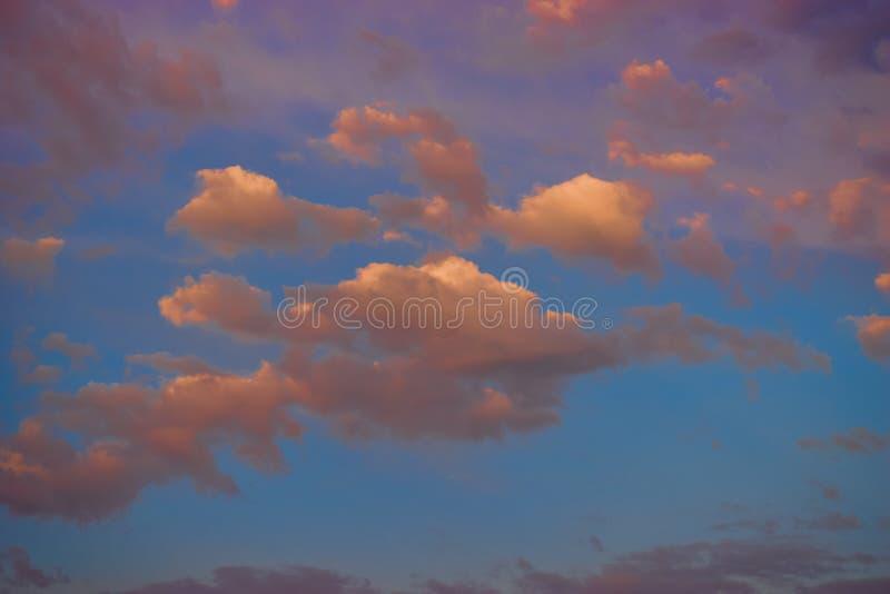 在日落的不可思议的桃红色云彩在背景 免版税库存照片
