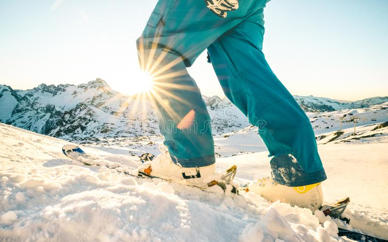 在日落的专业滑雪者腿在滑雪倾斜山区度假村 免版税库存图片