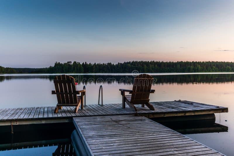 在日落的两把木椅子在镇静塞马湖lakein芬兰- 3的岸的一个码头 免版税图库摄影