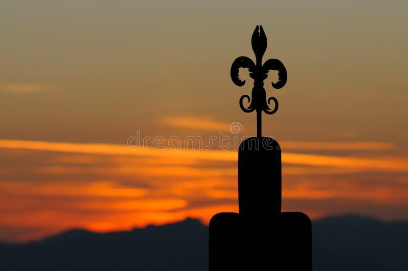 在日落的中世纪锻铁百合标志 Gubbio,意大利 库存图片