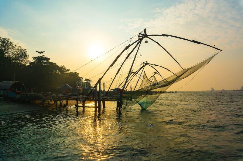 在日落的中国捕鱼网在科钦 免版税库存照片