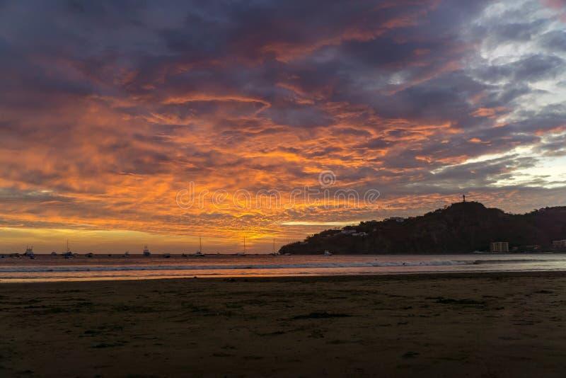 在日落的五颜六色的云彩在与小船的海滩 圣胡安del sur,尼加拉瓜 免版税图库摄影