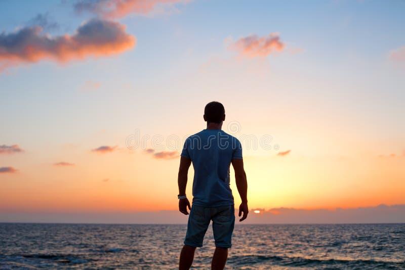 在日落的人剪影在海附近 库存照片