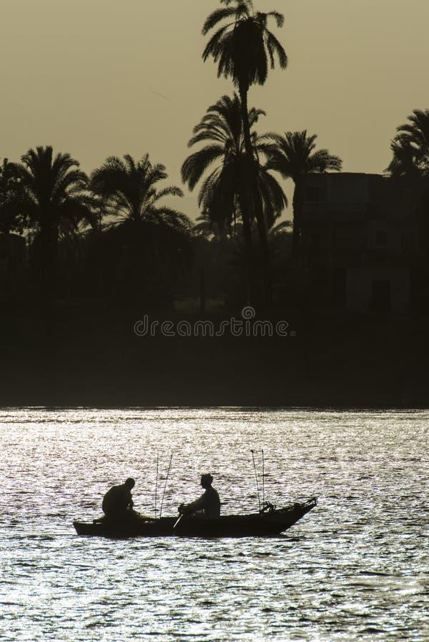 在日落的传统埃及流浪的渔夫剪影 库存照片