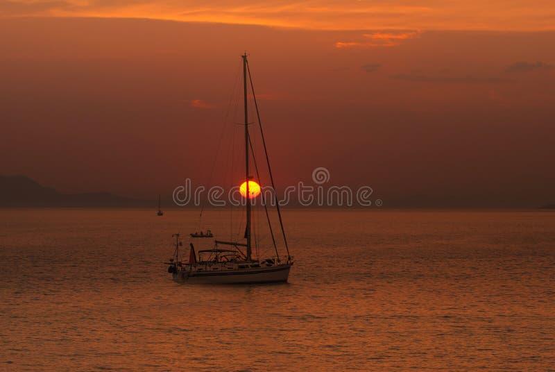 在日落的传统小船在科孚岛海岛 库存图片