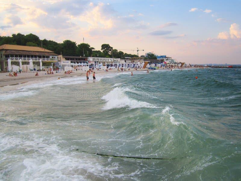 在日落的傲德萨、乌克兰- 2019年6月发光的明亮的色的云彩和黑海,朗热龙的快乐的波浪海滩 免版税库存照片