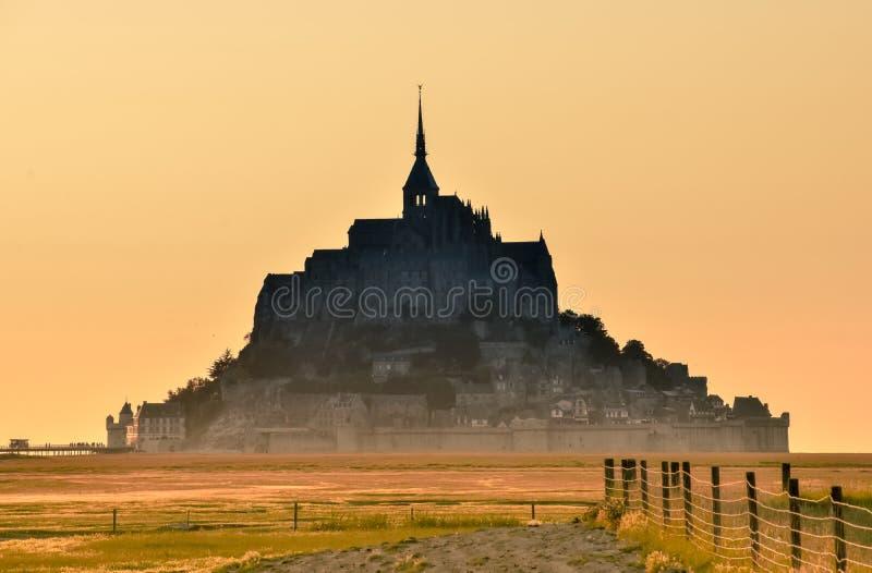 在日落的剪影从Mont圣米歇尔,法国农田  库存图片