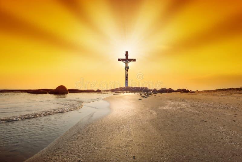 在日落的十字架在海滩背景 免版税库存图片