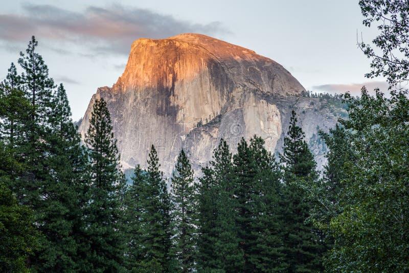 在日落的半圆顶在优胜美地国家公园,加利福尼亚,美国 免版税库存照片