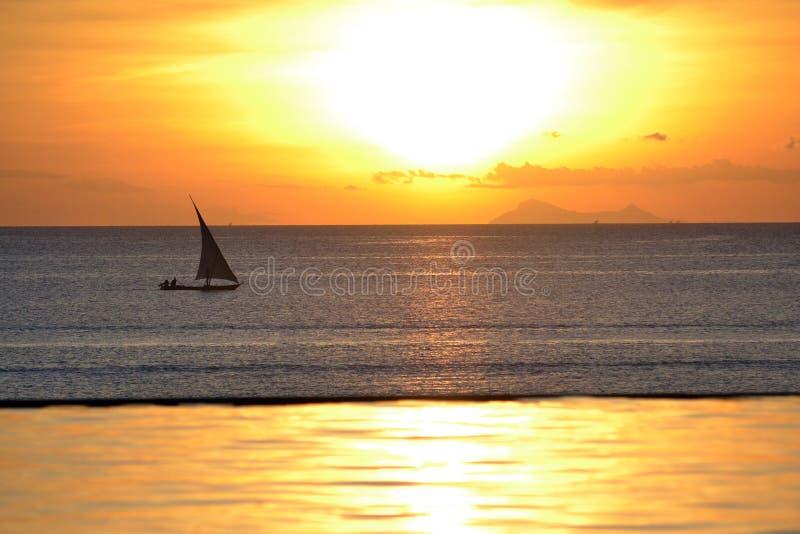 在日落的单桅三角帆船小船 库存照片