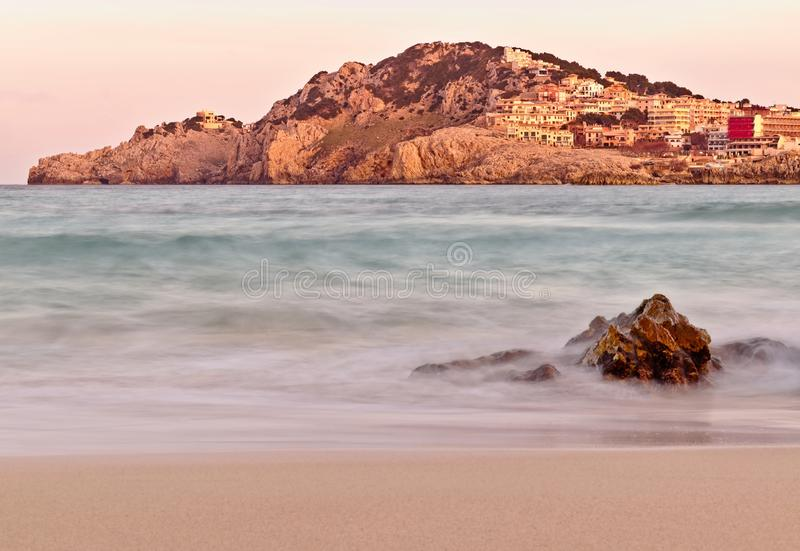 在日落的卡拉市Agulla海滩,与小山和镇加上岩石前景,马略卡,西班牙 库存图片