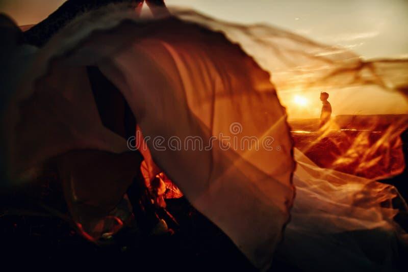 在日落的可爱的婚姻的夫妇 跑到她的新郎的新娘 bsckground的人 免版税图库摄影
