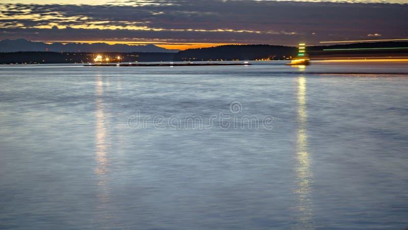 在日落的塔科马海湾与光从小船落后 免版税库存图片