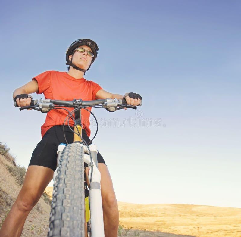 在日落的夏天期间一个登山车的一个被定调子的女孩在小山 库存照片