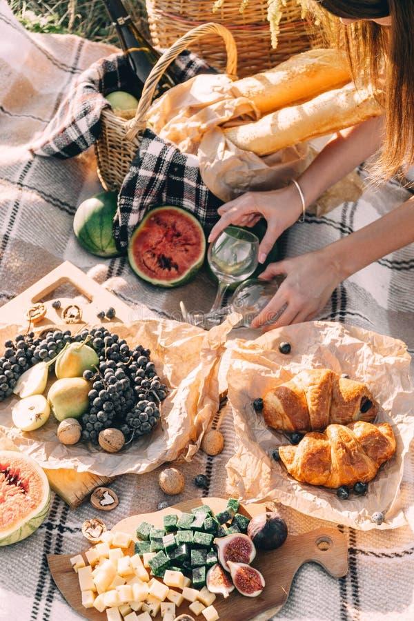 在日落的夏天野餐在格子花呢披肩、食物和饮料构想生活方式晴朗的天气 免版税库存照片