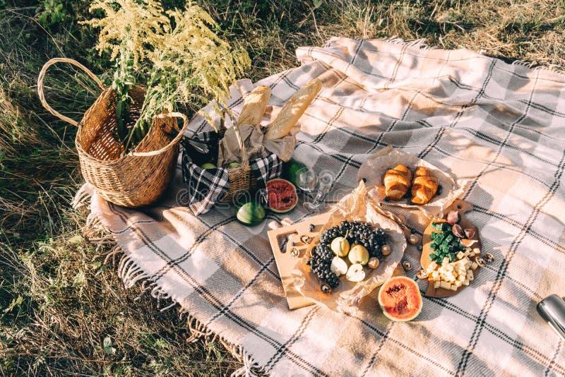 在日落的夏天野餐在格子花呢披肩、食物和饮料构想生活方式晴朗的天气 图库摄影