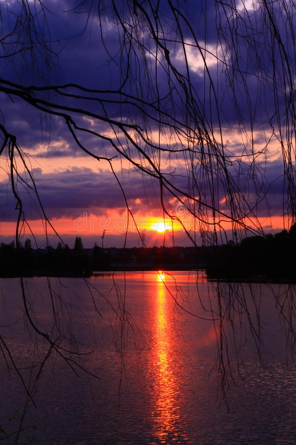 在日落的多云天空用美丽的桔子和蓝色在乡下 库存照片