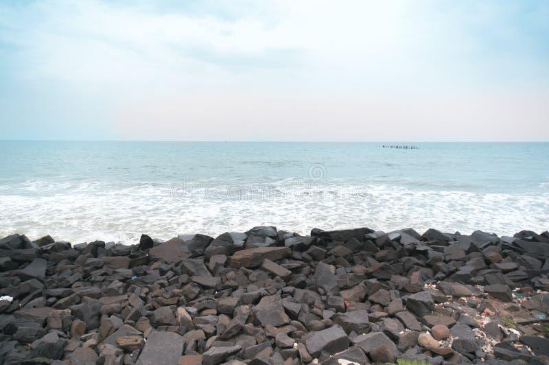 在日落的多岩石的海滩与波浪和多云天空 库存照片