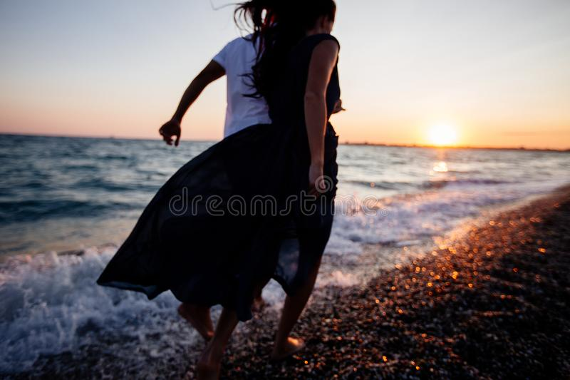 在日落的夫妇由海 库存照片