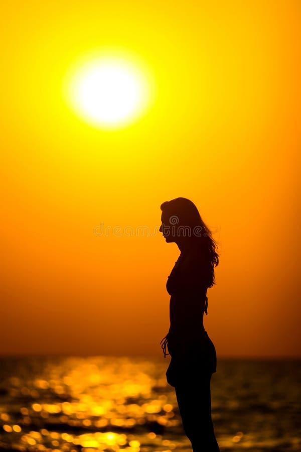 在日落的妇女剪影 库存图片