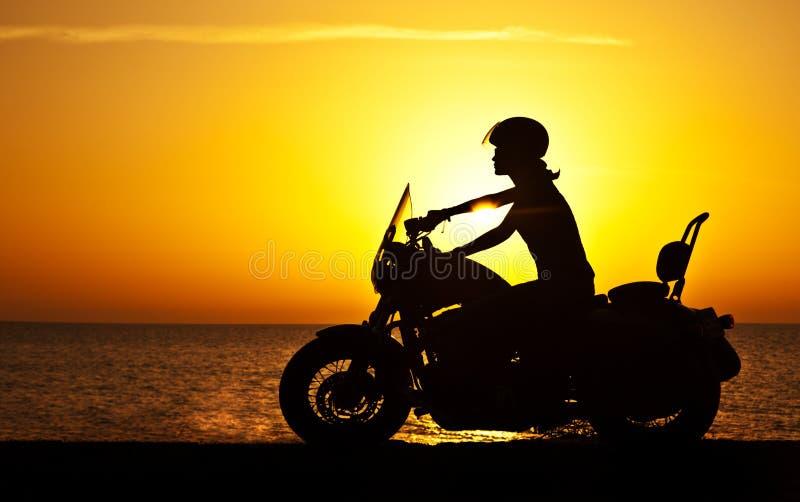 在日落的妇女骑自行车的人 免版税图库摄影