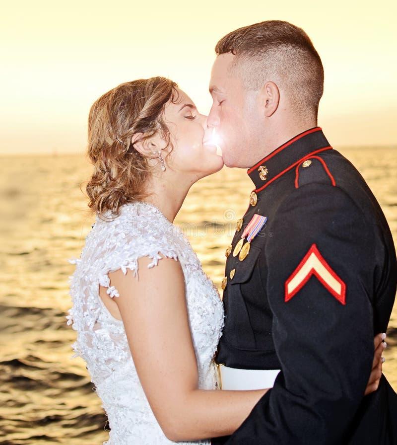 在日落的婚姻的亲吻 库存图片