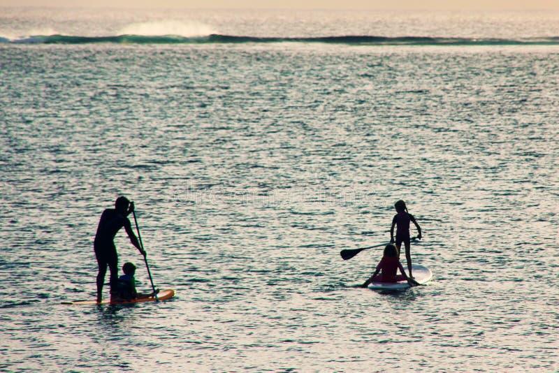 在日落的家庭剪影在海洋 Familysupping 免版税库存图片